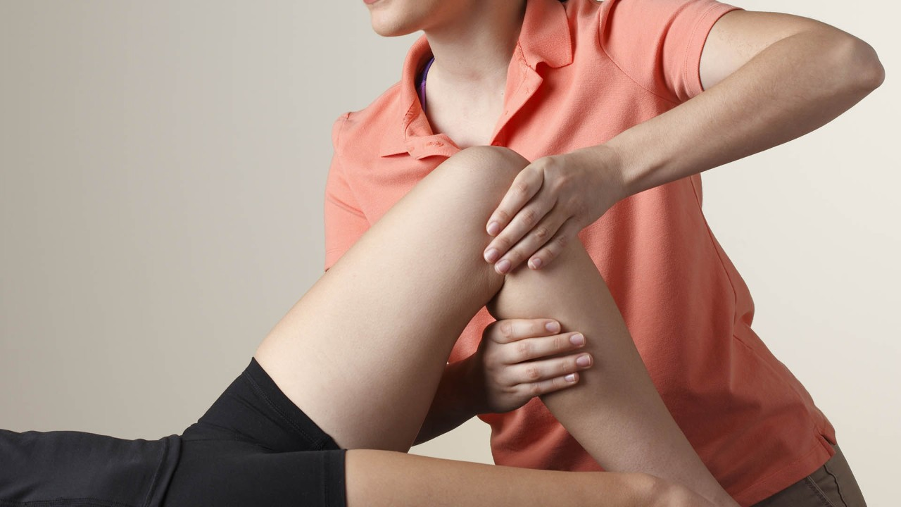 Physical Therapist Adjusting Patient's Knee
